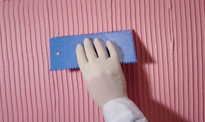 Проведение гребенкой по штукатурке на стене