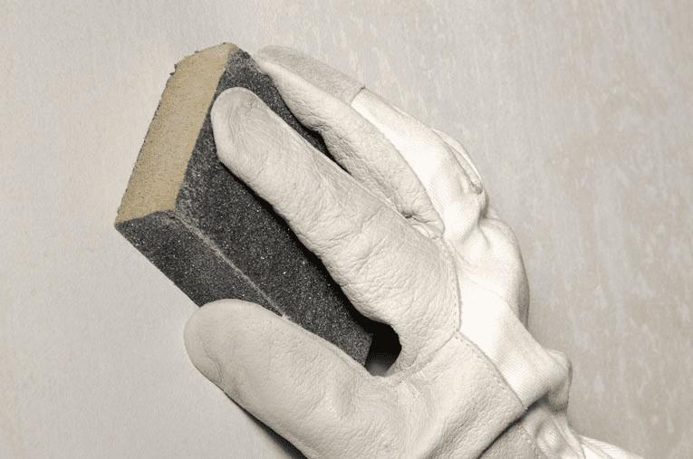 Обработанные штукатуркой углы шлифуют мелкодисперсной наждачкой после полного высыхания, удаляя пузырьки и мелкие неровности