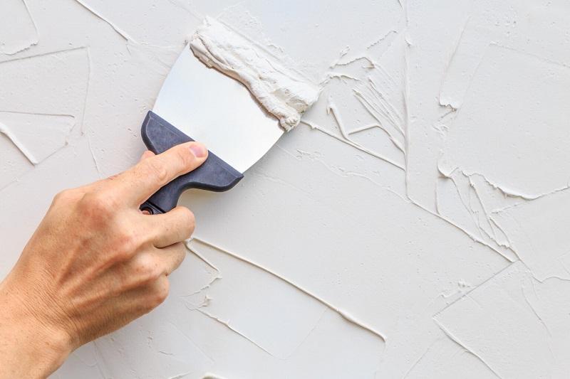 Второй слой штукатурки наносят на стены хаотичными короткими мазками