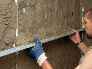 Материал накидывают на стену и разравнивают правилом по маячкам