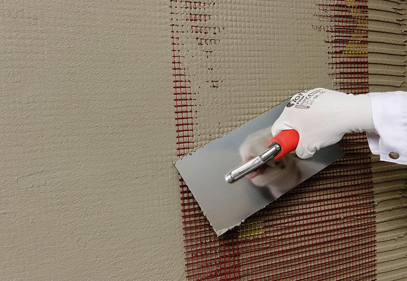 Штукатурка наносится на утеплитель слоем в 15 мм, далее крепится сетка и снова наносится слой