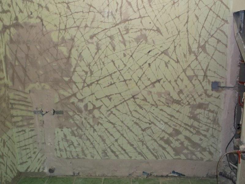 Чтобы штукатурка крепко держалась на поверхности, на бетонной стене делают засечки