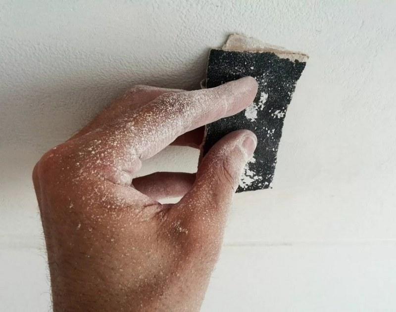 После нанесения финишного слоя поверхность шлифуют с помощью крупнозернистой наждачной бумаги