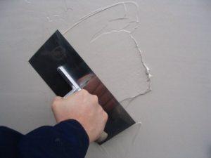 После застывания штукатурки стены шпаклюют финишным составом
