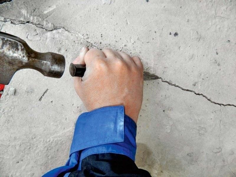Чтобы шпаклевка глубже проникла в трещины, их углубляют зубилом и молотком
