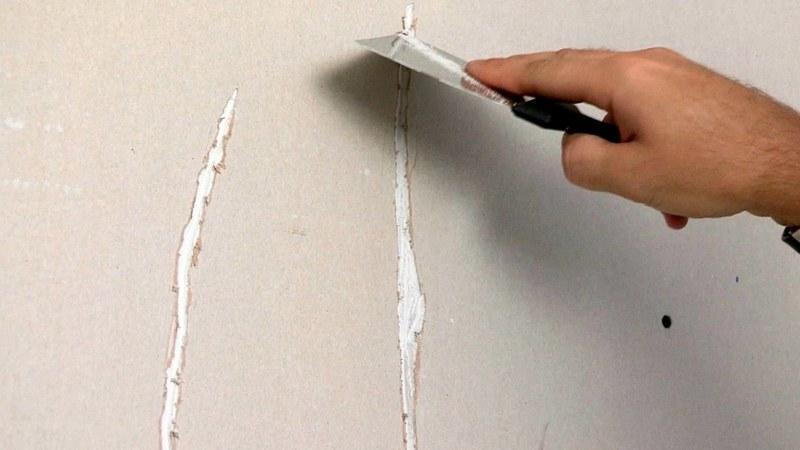 Мелкие трещины на поверхности стены заполняются шпаклевкой с помощью шпателя