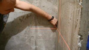 На стенах делают вертикальные отметки при помощи лазерного инструмента