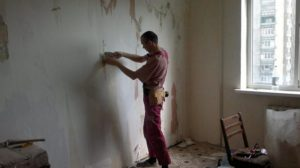 Очищают поверхность стены от мусора, предыдущей отделки