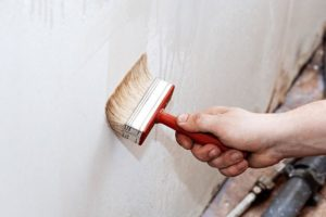 Кистью наносят на стену несколькими слоями накрывку