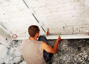 Маячок с помощью уровня выравнивают по вертикали и относительно углов стены
