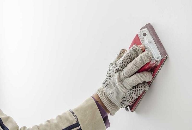 Ошкуривание стен после шпаклевки осуществляют с помощью наждачки или терки